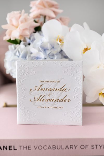 Luxury embossed wedding invitation in white and gold foil